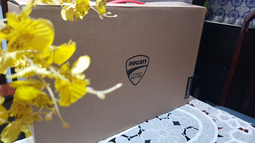 Caixa de papelão onde o notebook lenovo ducati 5 vem, com uma pequena alça vermelha que se assemelha a uma maleta.