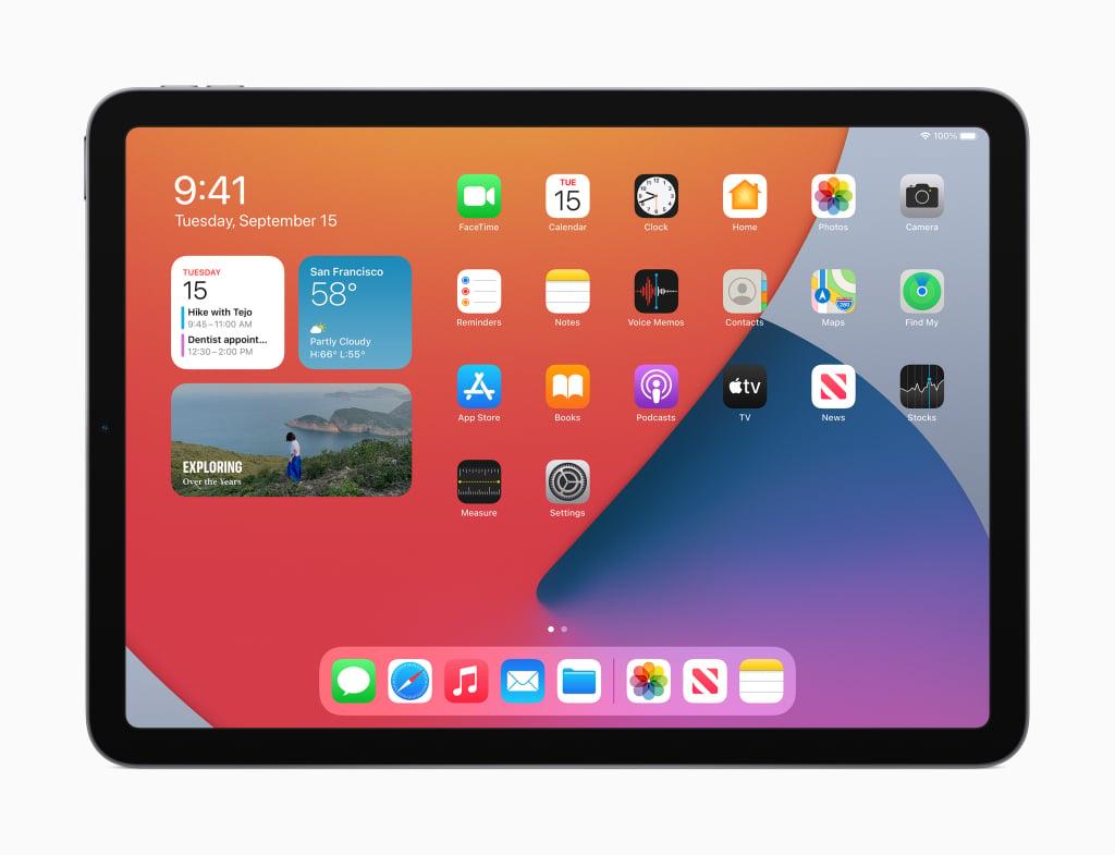 Tela inicial do ipad os 14 exibida em um ipad air 4ª geração. Coluna de widgets à esquerda, ícones de apps padrão do sistema à direita e a barra de tarefas com ícones abaixo.