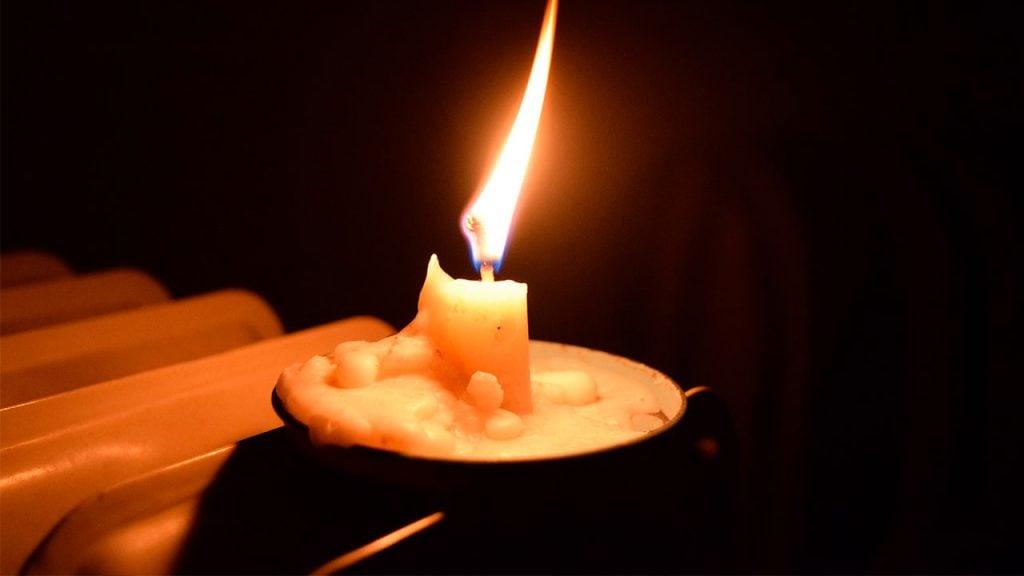 Vela sob um pires iluminando o ambiente, representativa da quantidade de luz emitida por uma vela num espaço de um metro quadrado.