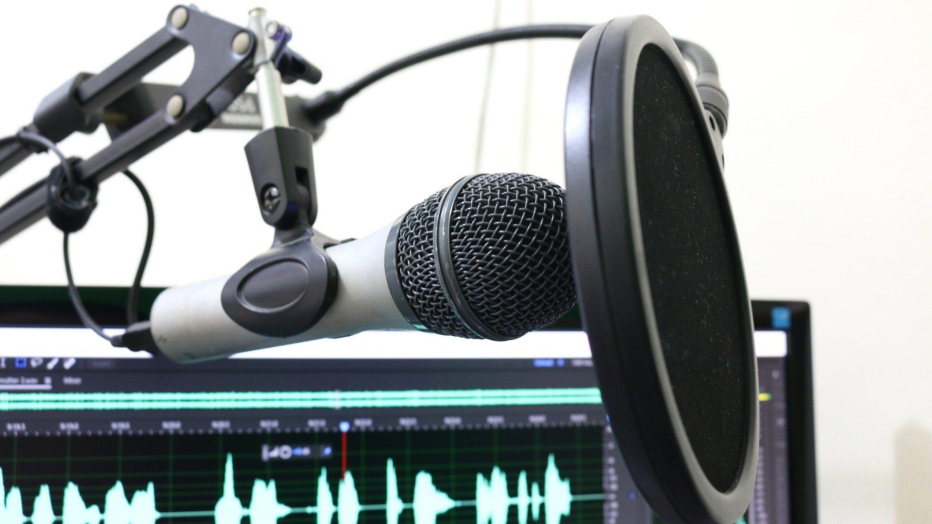 Microfone para podcasts em evidência na frente de um computador, provavelmente com algum programa de edição de áudio aberto