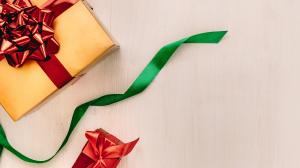 A imagem do texto, que aborda como economizar nas compras de natal, mostra presentes embrulhados em um fundo branco
