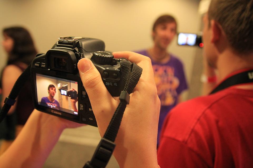 Câmera gravando um vídeo de um homem de camisa roxa.