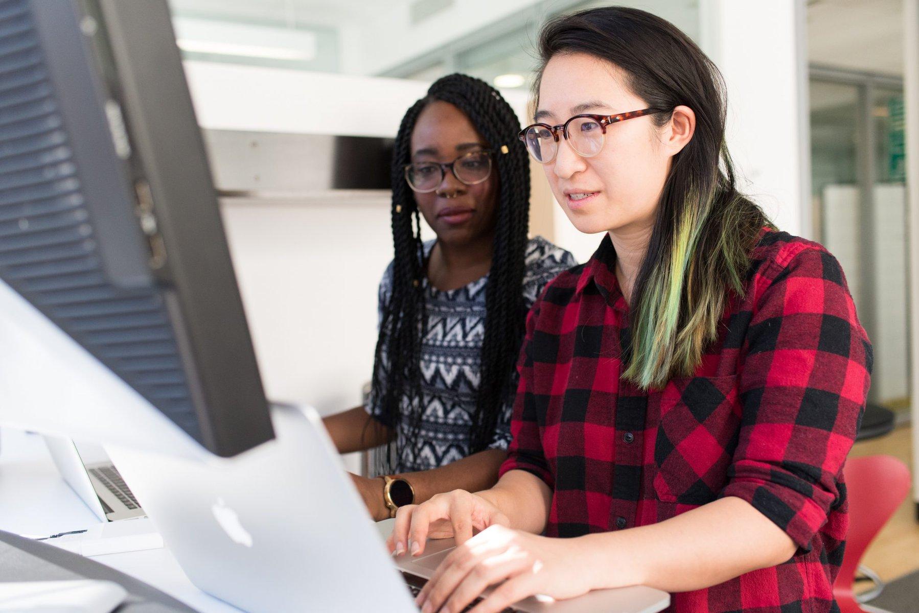 Imagem de capa; duas mulheres mexem no notebook e olham para um monitor.