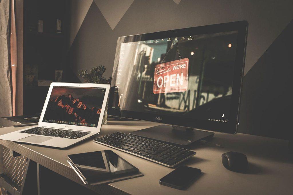 Sobre a mesa, computador, celular, tablet e um notebook; este último, transmitindo uma imagem para o monitor do computador para ilustrar como conectar seu notebook a um monitor