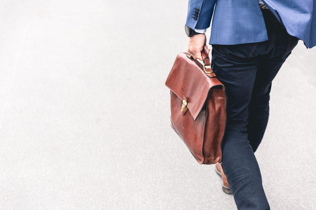 Pessoa caminhando com uma uma pasta de trabalho
