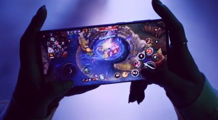Duas mãos seguram um celular enquanto joga league of legends: wild rift