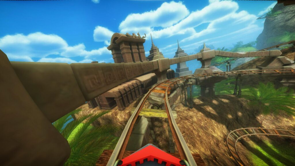 Trilho de montanha russa à frente de um carro, nuvens acima e construções e natureza ao redor.