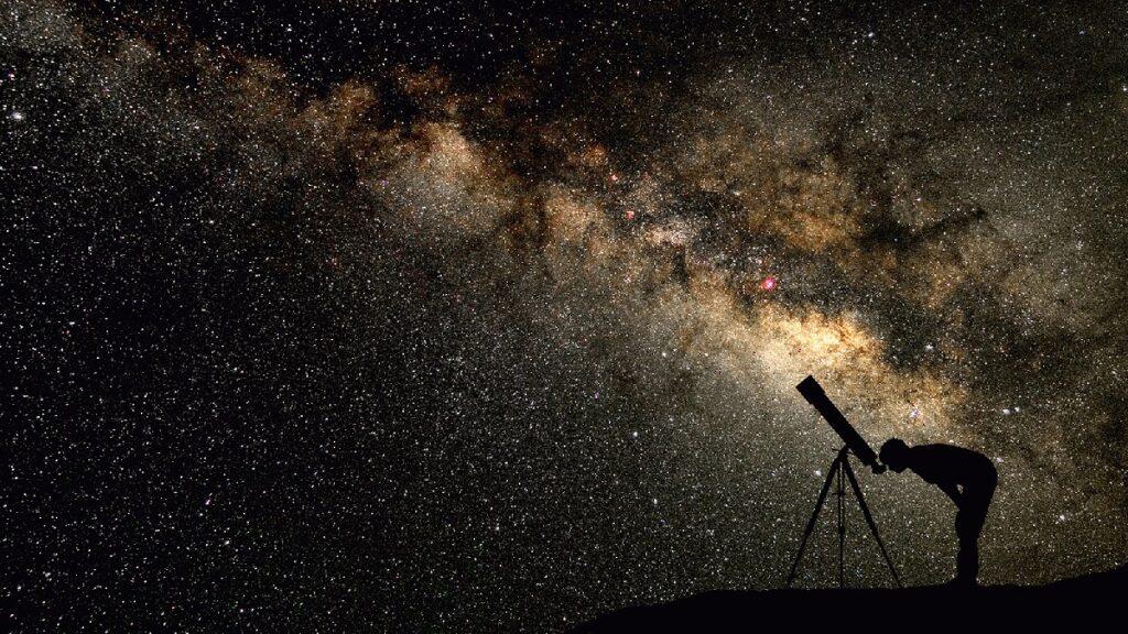 Pessoa olhando um céu estrelado através de uma luneta.