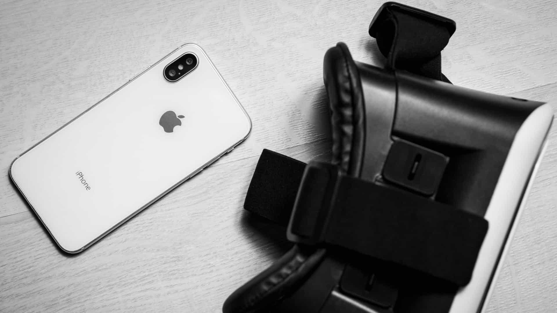 Iphone ao lado de óculos de realidade virtual.