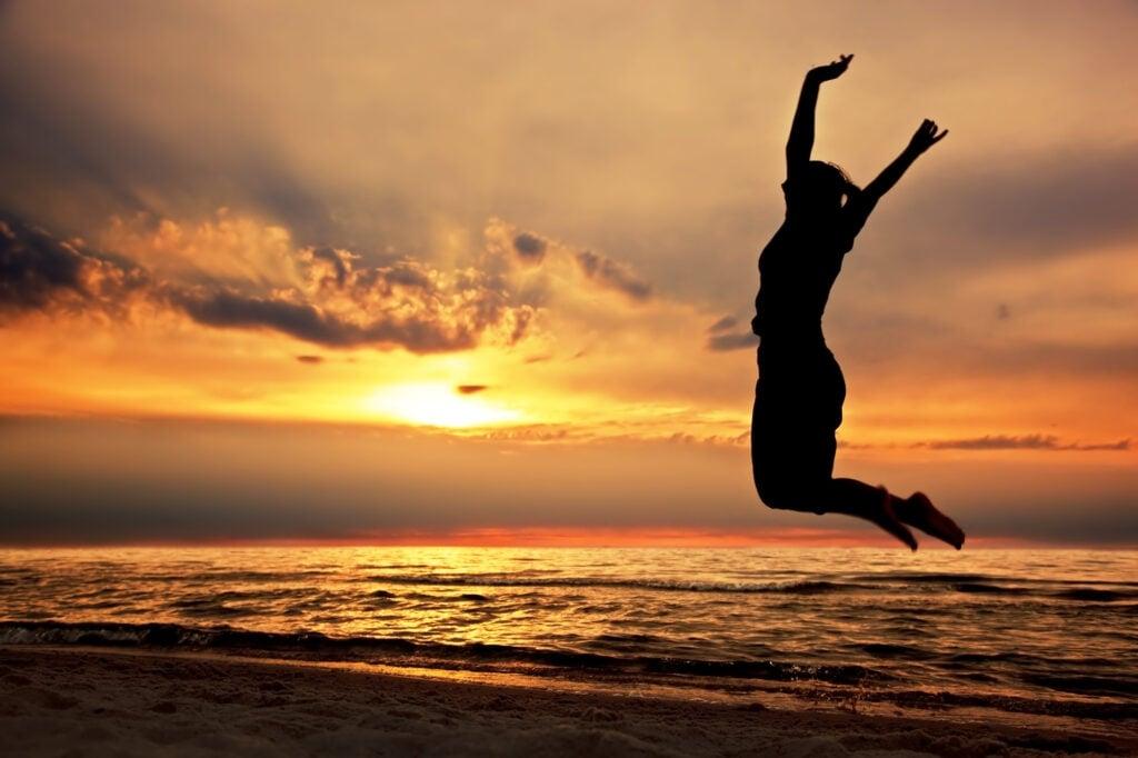 Mulher saltando na praia contra a luz