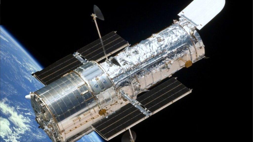 A imagem mostra o telescópio hubble no espaço sideral.