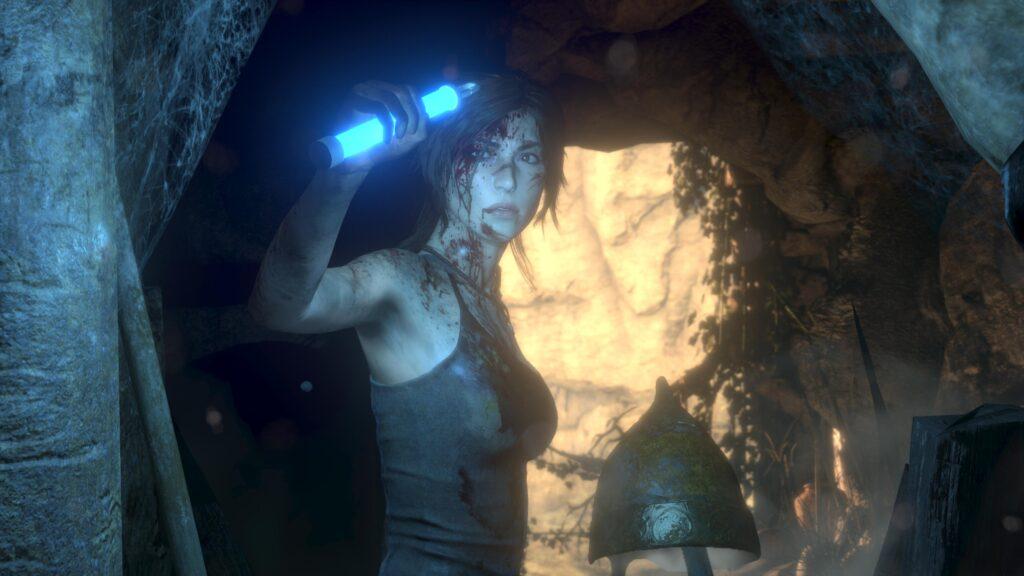 Lara croft, de lado e olhando em direção à tela, segura à altura da cabeça um dispositivo de iluminação azul.