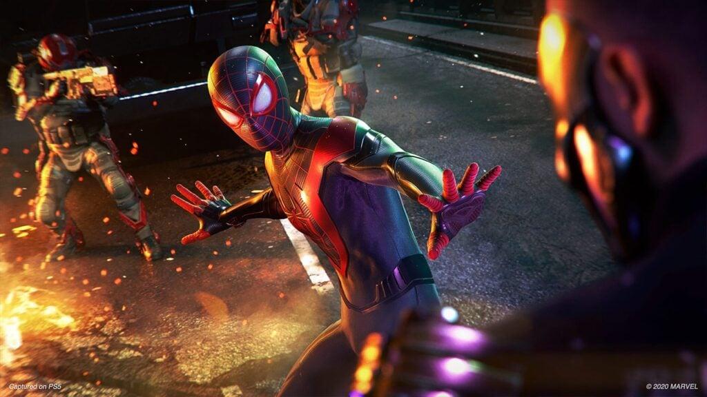 Spider-man enfreta trêss inimigos, dois deles estão armados; há fogo no cenário.