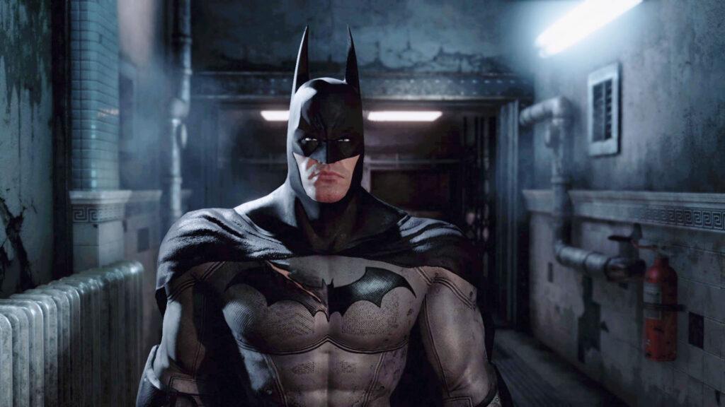 Batman em primeiro plano, ao fundo, instalação do manicômio arkham.