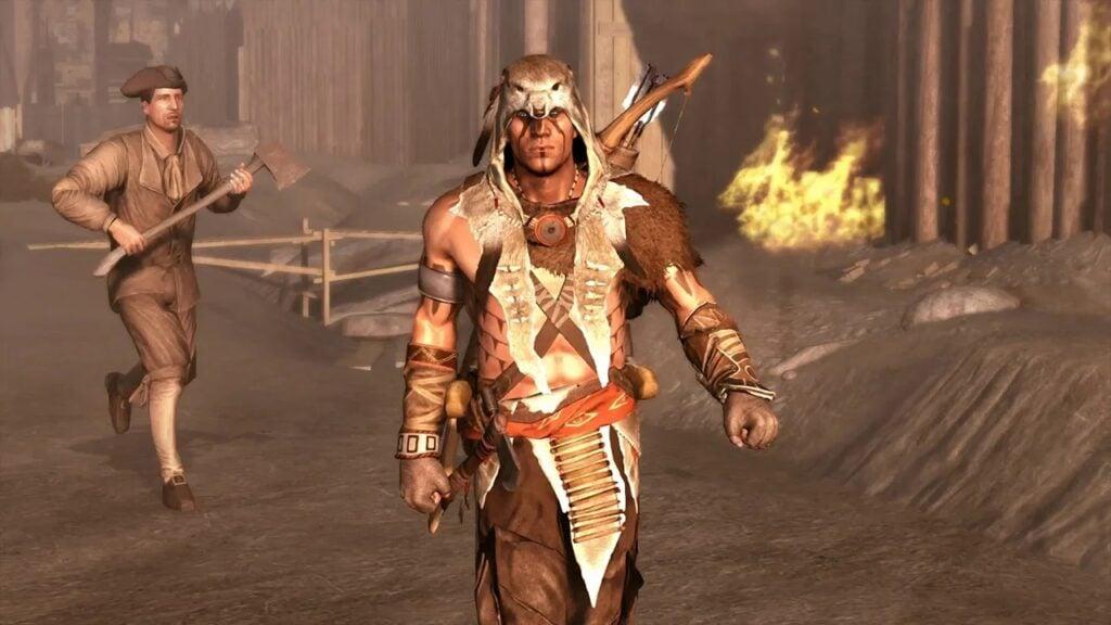 Connor, com vestes indígenas, anda em direção à câmera; ao fundo, casa em chamas.