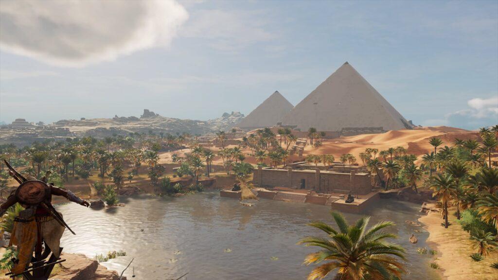 Duas pirâmides ao longe; uma cidade em um oásis em primeiro plano.