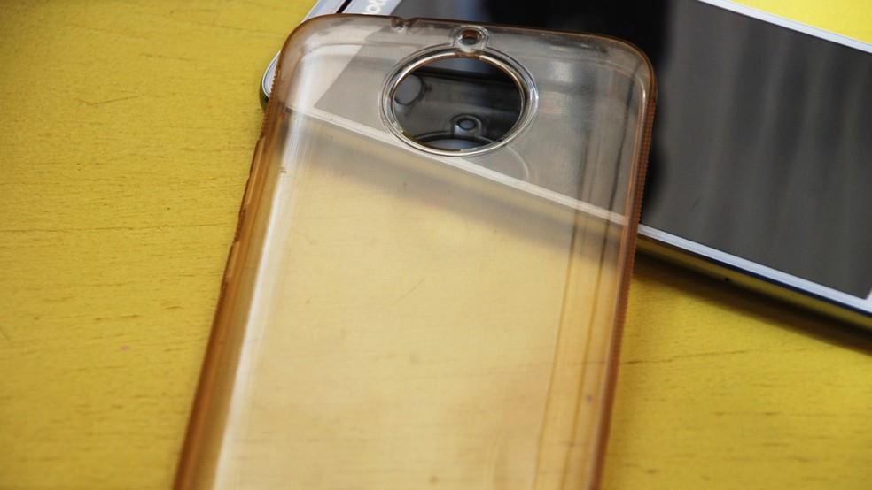 Celular com uma capa de silicone em cima de uma mesa de madeira
