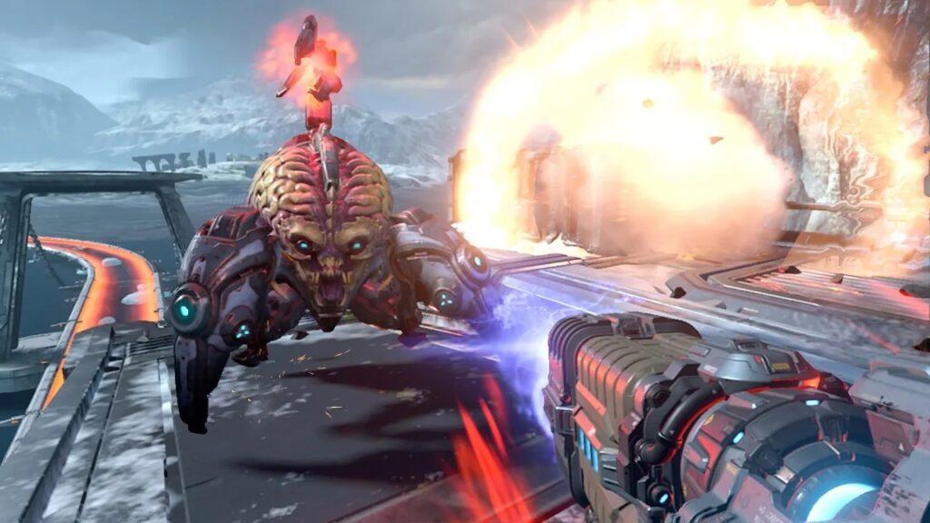 Doom guy, o protagonista, aponta uma arma de plasma em direção a um demônio aracnídeo.