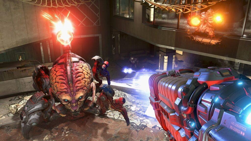 Doom guy aponta a arma de plasma para um demônio aracnídeo.