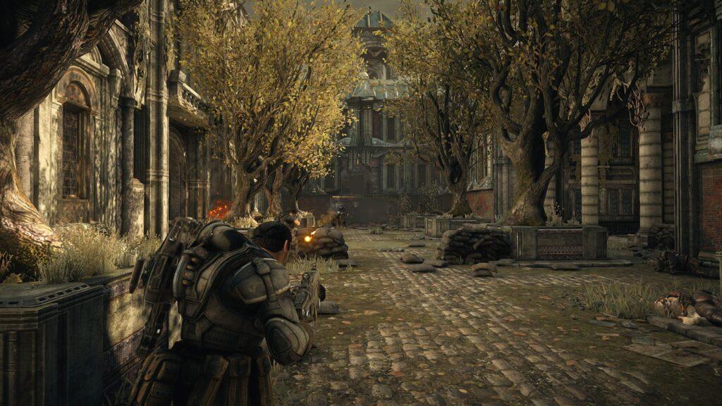 Construção ao fundo de um corredor, árvores dos dois lados, piso de pedra e, em primeiro plano e de costas, o protagonista de gears of war, empunhando uma arma.