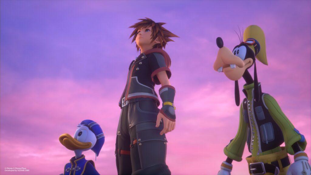 Olhando algum ponto não presente na tela, da esquerda para a direita: pato donald, sora e pateta.