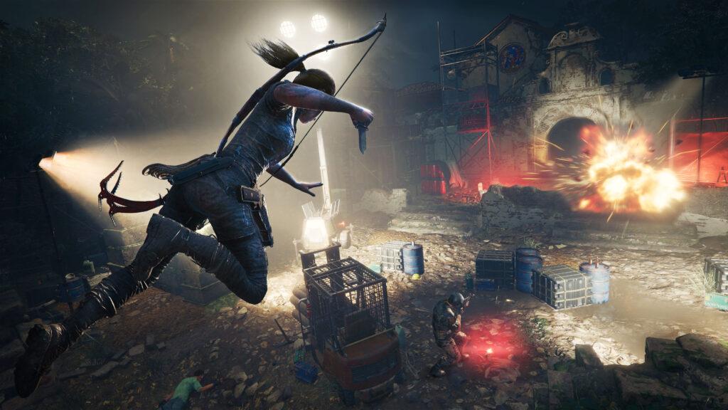 Lara croft salta, com faca na mão, do alto em direção a acampamento de inimigos.