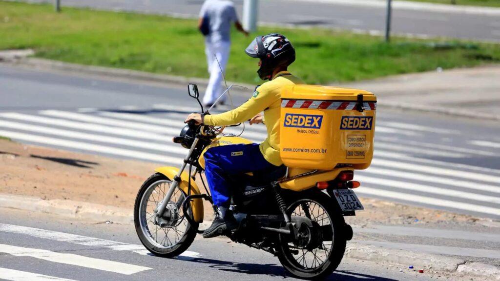 Motociclista fazendo entregas para o sedex hoje.
