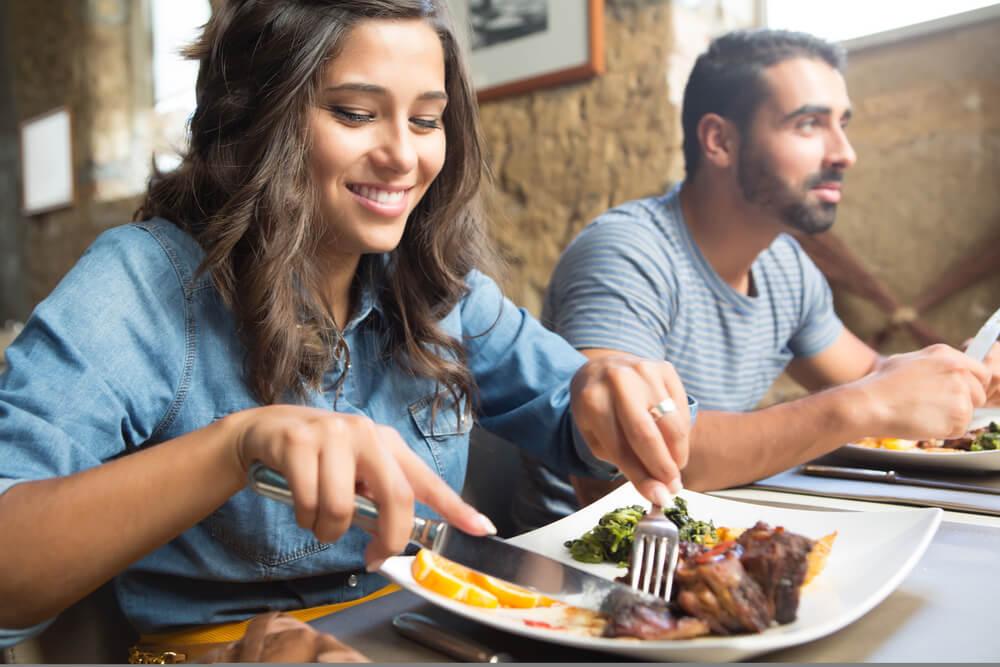 Mulher e homem comendo refeição preparada em casa