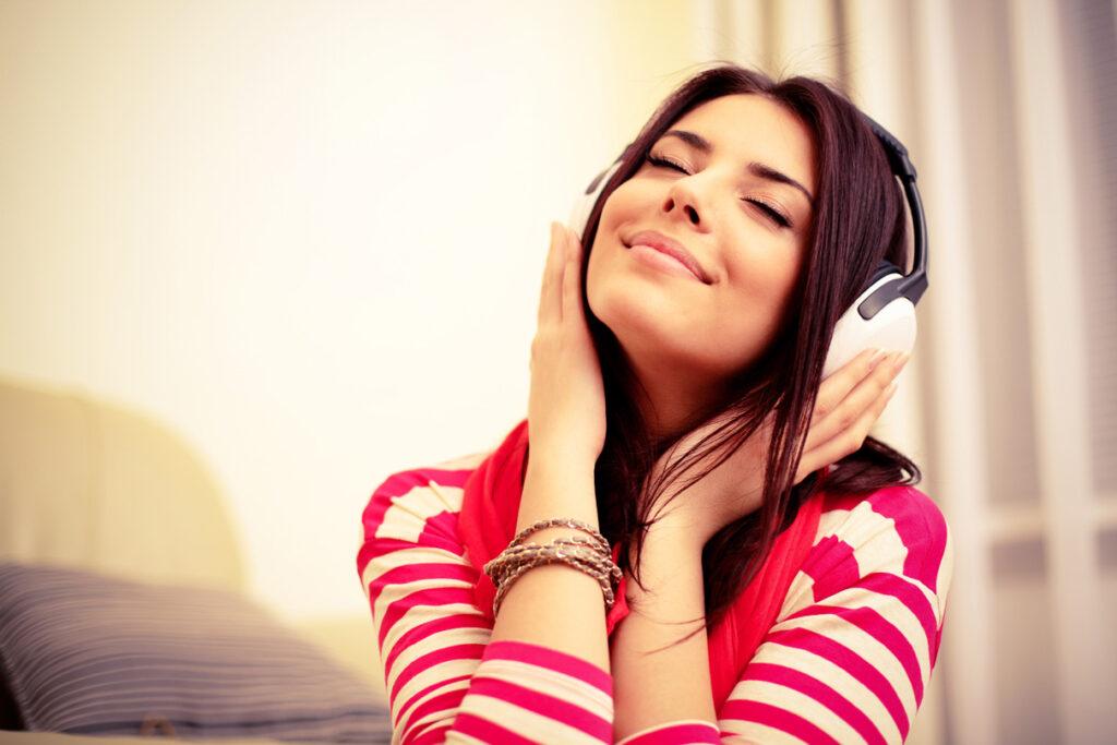 Mulher ouvindo música em um fone auricular branco