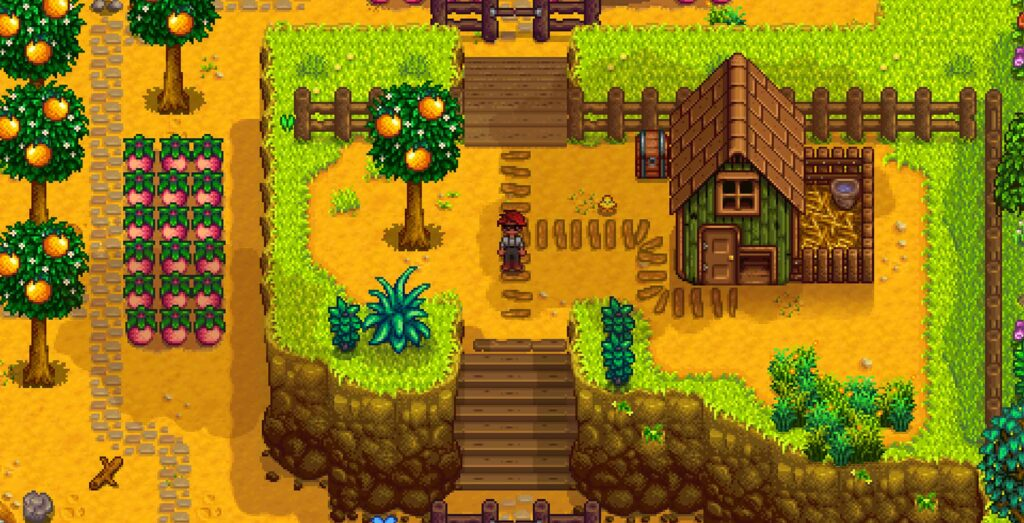 Imagem de stardew valley mostrando o protagonista do lado de uma casa em cima de um morro em sua fazenda e uma horta e um pomar abaixo do morro à sua esquerda