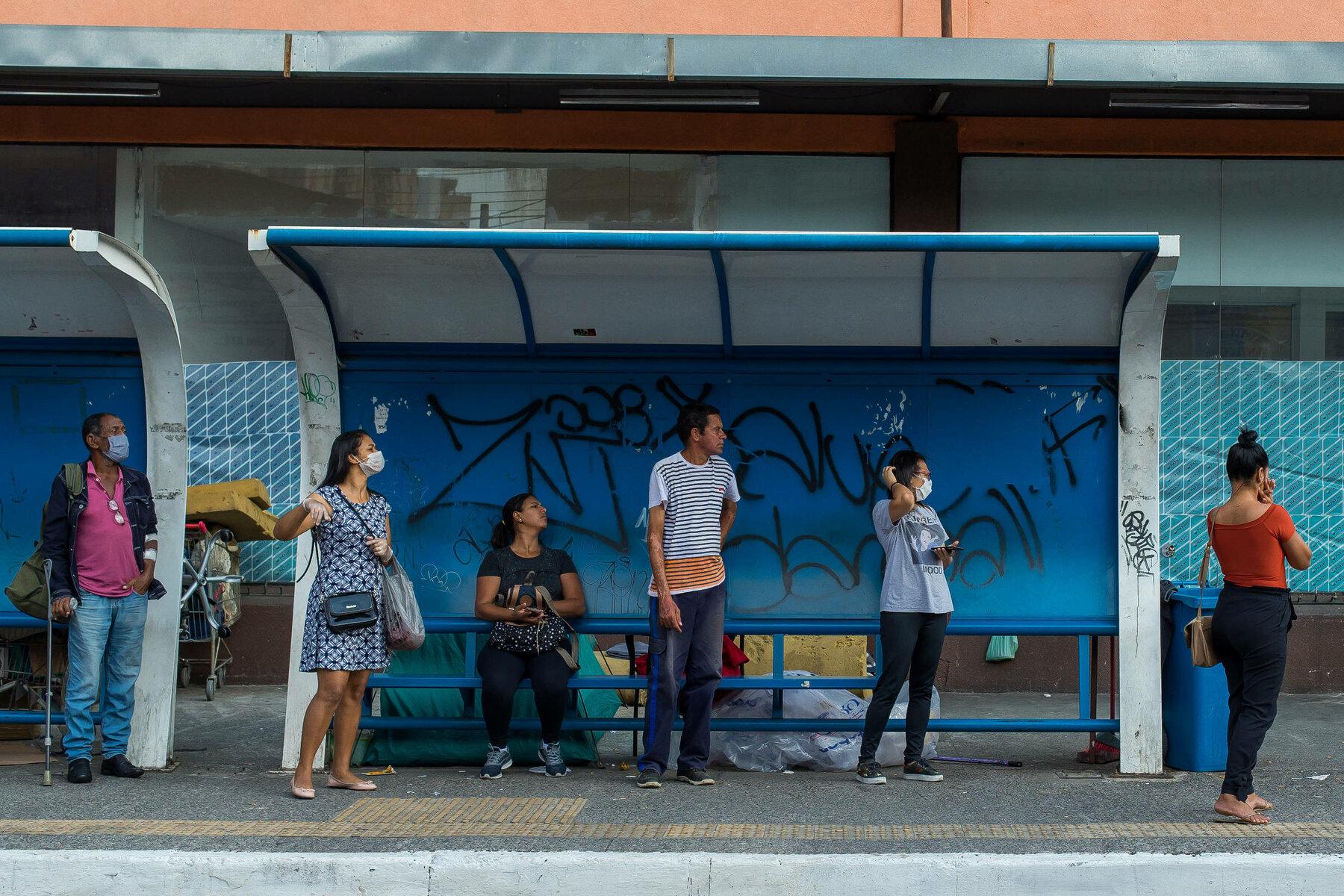 Pessoas em parada de ônibus durante pandemia