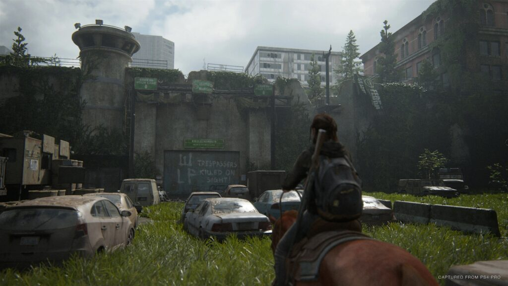 Ellie, montada em um cavalo, chega a uma construção abandonada.