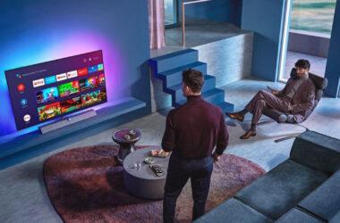 Homem olhando tvs com android