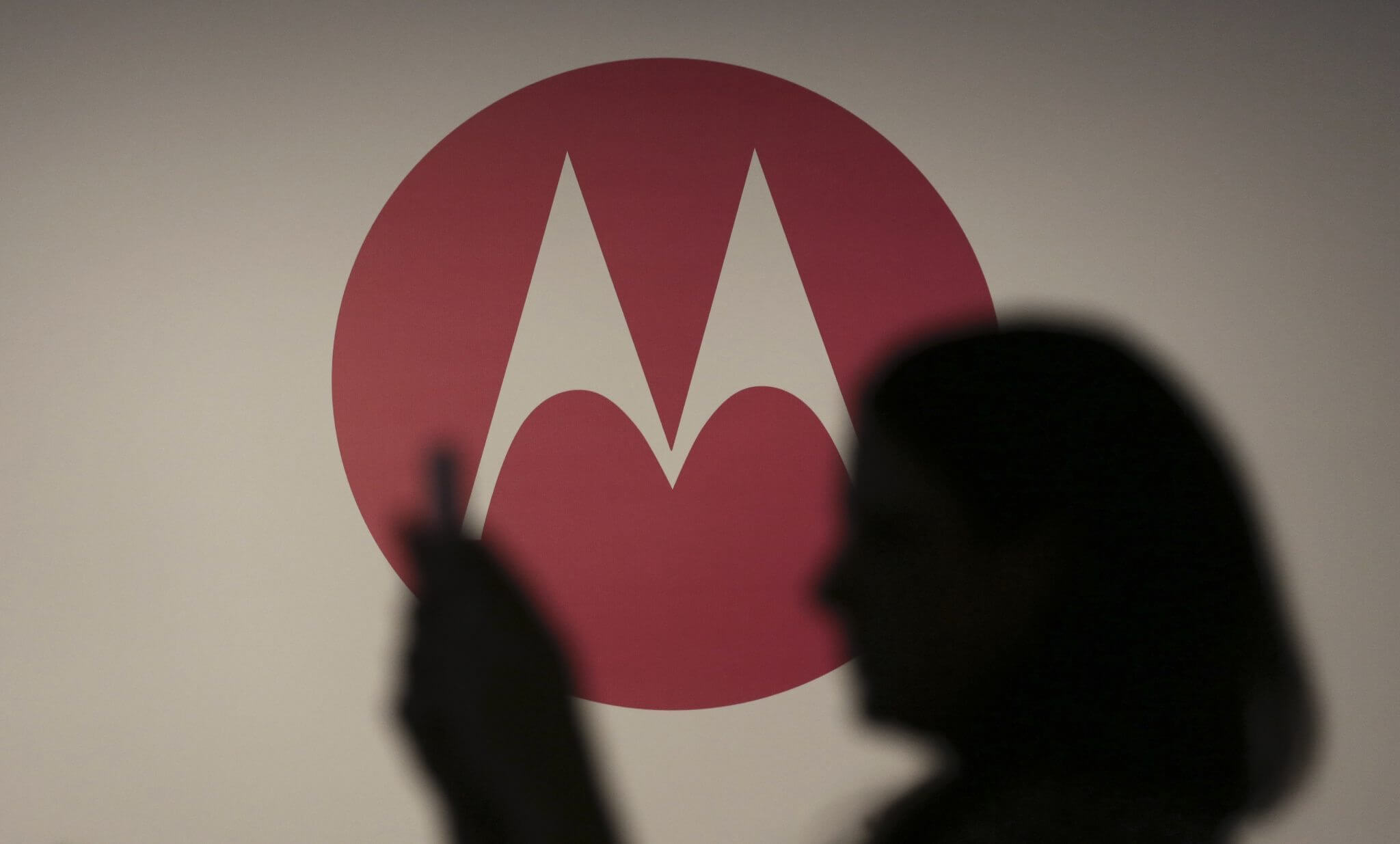 A woman takes a picture in front of a Motorola logo before the worldwide presentation of the Moto G mobile phone in Sao Paulo November 13, 2013. The new Motorola phone, which is being aimed at consumers in developing markets like Brazil and India as well as budget-buyers in Western countries, is the second major new product that Motorola has developed since its acquisition by Internet company Google in 2012. REUTERS/Nacho Doce (BRAZIL - Tags: BUSINESS LOGO TELECOMS) - RTX15BYF